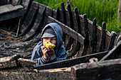 A Boy Eats An Apple In A Derelict Wooden Boat, Danube Delta In April, Mila 23, Tulcea, Romania.