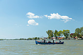 Danube Delta, a boat sets off over the Sulina arm, Sulina, Tulcea, Romania.