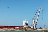 Danube Delta, ducks fly over crane and ship in the port of Sulina, Tulcea, Romania.