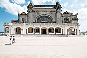 Two women stroll in front of the Old Casíno of Constanta on the Black Sea, Constanta, Romania.