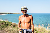 Shepherd with a shirtless captain's hat, Black Sea coast, holding pretzel sticks in his hand, Costinesti, Constanta, Romania.