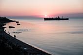The shipwreck Evangelia, people and seagulls at sunrise on the Black Sea coast in Costinesti, Constanta, Romania.