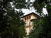Quartiere Coppeda, Rome, Italy: tower of a building, seen through green branches from the street