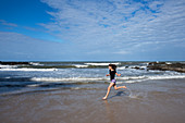 Young woman running on Havaisinho Beach near Itacaré, Bahia, Brazil, South America