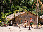 Indigenous family in front of residential house on the Amazon near Manaus, Nucleo Cultural Indigena Cipia, Amazon basin, Brazil, South America