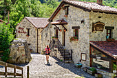 Woman hiking goes through village of Bulnes, Bulnes, Picos de Europa, Picos de Europa National Park, Cantabrian Mountains, Asturias, Spain