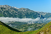 View of Picos de Europa with foggy mood in the valley, from Picu Tiedu, Picos de Europa, Picos de Europa National Park, Cantabrian Mountains, Asturias, Spain