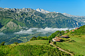 View of Picos de Europa and alpine settlement with foggy mood in the valley, from Picu Tiedu, Picos de Europa, Picos de Europa National Park, Cantabrian Mountains, Asturias, Spain