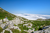 Woman while hiking sits on rock and looks at sea of fog, from Picu Tiedu, Picos de Europa, Picos de Europa National Park, Cantabrian Mountains, Asturias, Spain