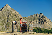 Woman stands in front of information boards at the Col d´Izoard pass, Cottian Alps, Hautes-Alpes, France