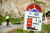 Information board for cyclists at Col du Galibier with cyclists out of focus in the background, Col du Galibier, Hautes-Alpes, Savoie, France
