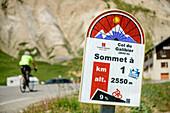 Infotafel für Radfahrer am Col du Galibier mit Radfahrer unscharf im Hintergrund, Col du Galibier, Hautes-Alpes, Savoie, Frankreich