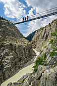 Three people stand on the Aletsch suspension bridge, Aletsch suspension bridge, UNESCO World Heritage Site Jungfrau-Aletsch, Bernese Alps, Switzerland