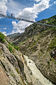Woman hiking goes over Aletsch suspension bridge, Aletsch suspension bridge, UNESCO World Heritage Site Jungfrau-Aletsch, Bernese Alps, Switzerland