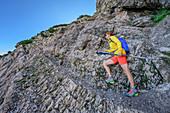 Woman hiking climbs over rocks to the Sonntagshorn, Sonntagshorn, Chiemgau Alps, Chiemgau, Upper Bavaria, Bavaria, Germany