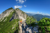 Woman hiking climbs over the ridge to the Sonntagshorn, Reifelberge in the background, Sonntagshorn, Chiemgau Alps, Chiemgau, Upper Bavaria, Bavaria, Germany