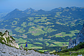 Woman mountaineering descends through the Egersgrinn from the Pyramidenspitze, view of Chiemgau Alps, Pyramidenspitze, Kaiser Mountains, Tyrol, Austria