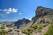 Man and woman while hiking take a break, Soiernspitze in the background, Soiernspitze, Karwendel, Upper Bavaria, Bavaria, Germany