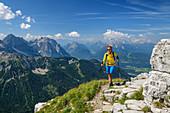 Woman hiking climbs up to Soiernspitze, Wörner, Westliche Karwendelspitze, Ahrnspitzen and Wetterstein with Zugspitze in the background, Soiernspitze, Karwendel, Upper Bavaria, Bavaria, Germany
