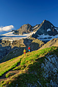 Man and woman hiking down from the Figerhorn, Grossglockner in the background, Figerhorn, Glockner Group, Hohe Tauern, Hohe Tauern National Park, East Tyrol, Austria