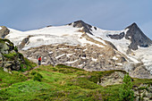 Woman hiking climbs to the Neue Prager Hut, Hoher Zaun and Schwarze Wand in the background, Venediger Group, Hohe Tauern, Hohe Tauern National Park, East Tyrol, Austria