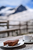 Coffee and cake with mountain out of focus in the background, Neue Prager Hütte, Venedigergruppe, Hohe Tauern, Hohe Tauern National Park, East Tyrol, Austria