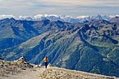 Woman hiking descends from the Großer Muntanitz, Großer Muntanitz, Granatspitzgruppe, Hohe Tauern, Hohe Tauern National Park, East Tyrol, Austria