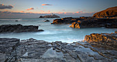 Sunset over Godrevy Lighthouse on Godrevy Island in St Ives Bay with the beach and rocks in foreground, Cornwall, UK