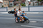 Street scene with a family riding on a motor scooter in Shanghai, China.