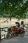 A Chinese rickshaw driver is resting at a park in Chengdu, Sichuan Province in China.
