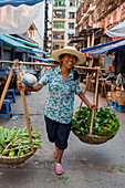 A woman is carrying produce on a carrying pole, also called a shoulder pole, over the shoulders in the city of Fengdu on the Yangtze River in China.