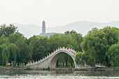 View over Kunming Lake towards a stone bridge and Jade Spring Hill with Jade Peak Pagoda at the Summer Palace, which was the imperial garden in Qing Dynasty, in Beijing, China.