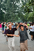 Chinese people exercising by dancing in a park near the Temple of Heaven in Beijing, China.