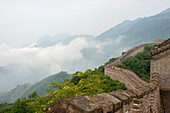 View of a section of the Great Wall of China in the mist at Mutianyu located in Huairou County 70 km northeast of central Beijing, China.