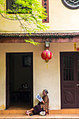 Woman reading in temple, Hanoi, Vietnam