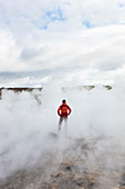 Woman standing by geothermal pools, Iceland