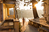 Woman making her way through temple to Pichola Lake in the early morning, Udaipur, Rajasthan, India