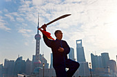 Practising Tai Chi with sword, with Pudong skyline, early morning, Shanghai, China