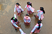 Long Horn Miao children dancing in a circle, Sugao, China