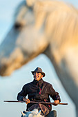 Camargue, France. Cowboy on horseback holding a cattle prod and smiling.