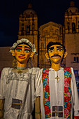 Giant puppets dressed as a bride and groom during a Calenda, a procession through the streets of downtown Oaxaca, celebrating a wedding in the city of Oaxaca de Juarez, Oaxaca, Mexico.