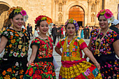 Women posing dressed in regional costumes in the city of Oaxaca de Juarez, Oaxaca, Mexico.