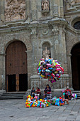 People selling balloons on the square in front of the Cathedral of Our Lady of the Assumption built in a neoclassical style, in the city of Oaxaca de Juarez, Oaxaca, Mexico.