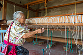 An old Zapotek woman is preparing a loom for weaving a carpet at a weavers home studio in Teotitlan del Valle, a small town in the Valles Centrales Region near Oaxaca, southern Mexico.