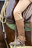 Close up of an Italian cowboy's boot in stirrup on horse, Tuscany, Italy