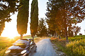 Car passing by on dirt road in Tuscany, Italy