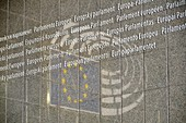 European Parliament Building, Brussels, Belgium. All the languages of the EU and reflection of the Parliament symbol at the main entrance