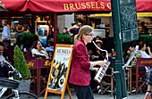 Young female busker playing the melodica in central Brussels, Belgium.
