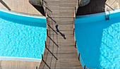 Top view of a boy walking on a wooden bridge over a swimming pool, Vilamoura, Portugal