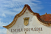 Facade of an old school with coat of arms and curved roof, near Sagres, Algarve, Portugal